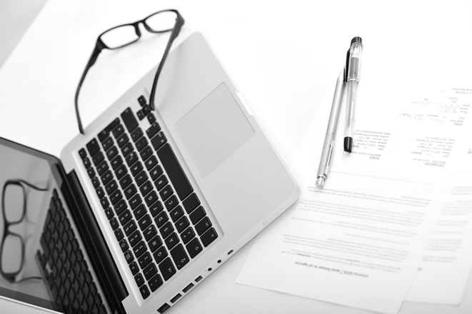 Laptop on desk with paper, pens an glasses